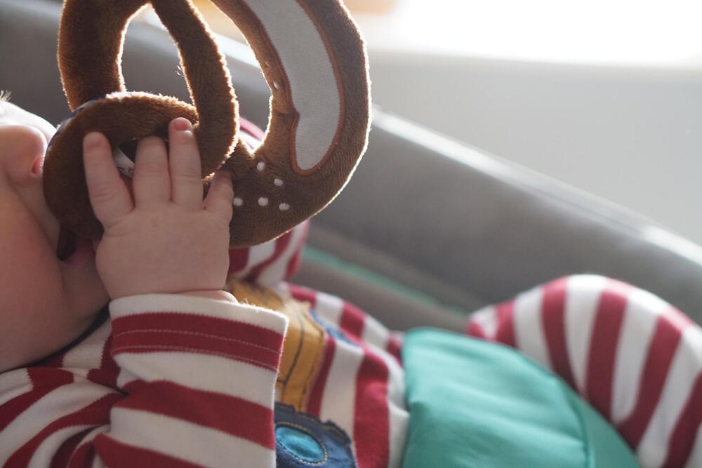Baby mit Spielzeug Brezel
