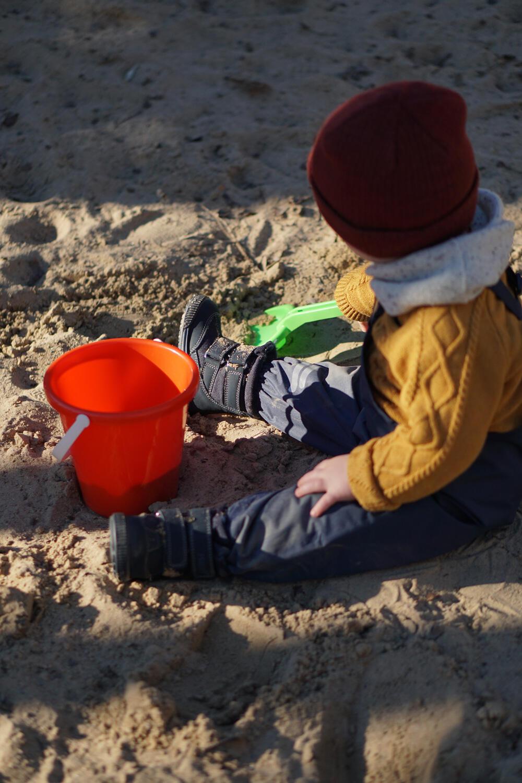 Kleinkind Spielplatz Buddeln Buddelkasten Sandkasten Eimer Schippe Frühling