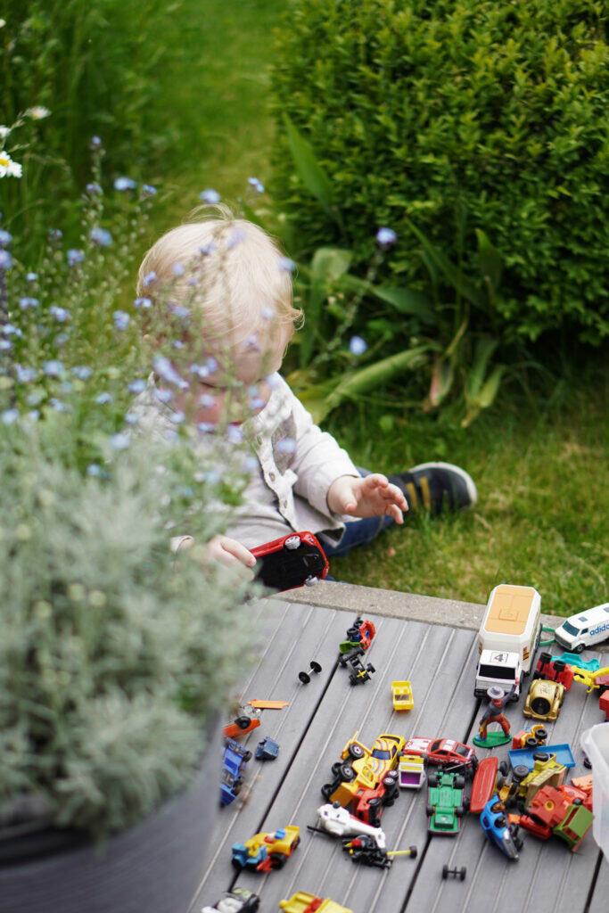 Kleinkind Garten Spielzeug Spielzeugautos spielen Terrasse