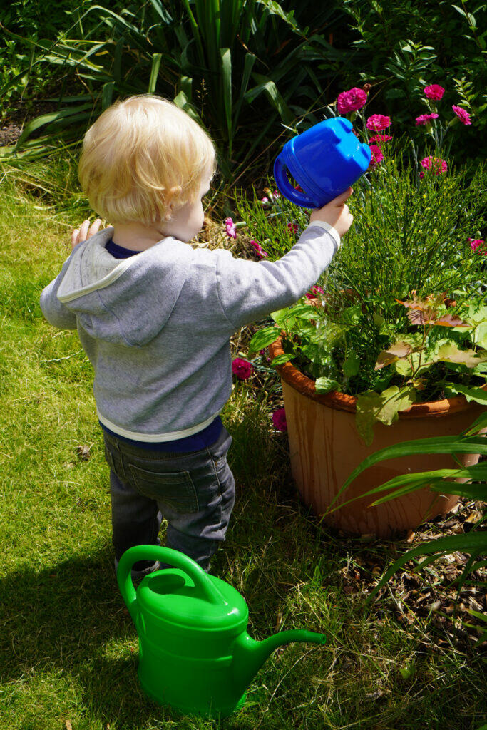 Kleinkind Junge Gießkanne Garten