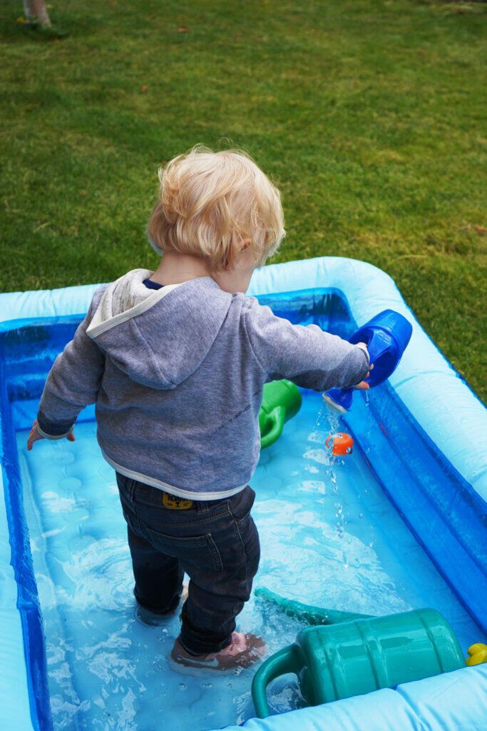 Kleinkind Pool angezogen Gießkanne