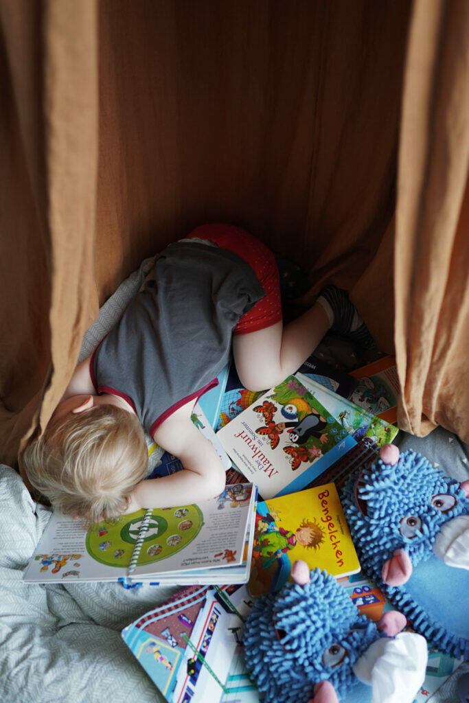 Kleinkind Junge blond Bücher Mittagsschlaf schlafen